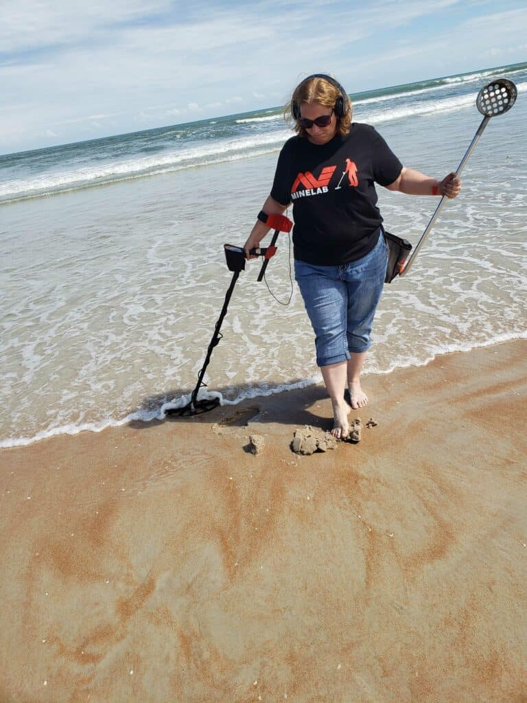Woman wearing headphones using Minelab metal detector on shore line