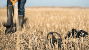 metal detecting in a farm field with a shovel