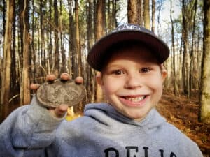 Little Dirt Diggers holds up a find in the woods