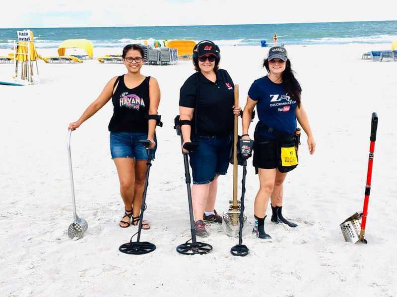 Three people go metal detecting on the beach in Florida.