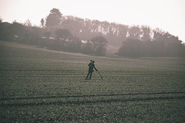 A man metal detects in a field.