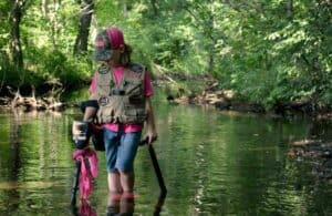 Lil Dirt Digger, a young metal detectorist, going underwater metal detecting in a stream