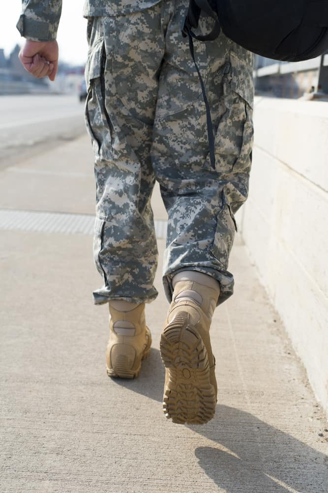 A veteran walks down the sidewalk with a backpack.